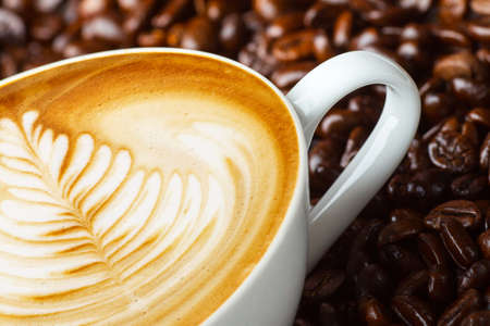 Latte art, coffee in coffee beans background Stock Photo