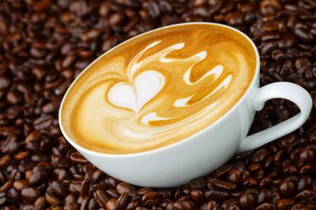 カフェラテ アート、コーヒー豆のバック グラウンドでコーヒー 写真素材
