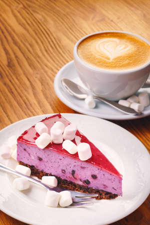 Cup of fresh hot coffee with delicious piece of blueberry cake on the wooden table