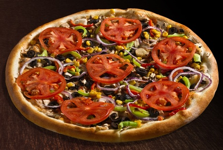 Vegetarian pizza with tomatoes, bell pepper, corn, olives, mushrooms and onion - isolated