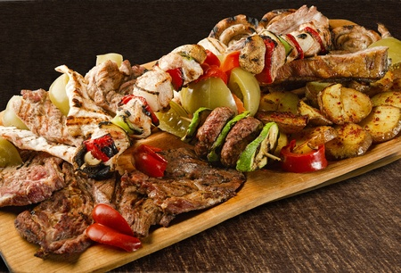 Rustic tray with various meats, mushrooms and assorted vegetables - isolated