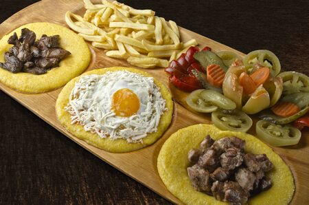 Rustic tray with various meats, baked egg, liver and assorted pickles- isolated photo
