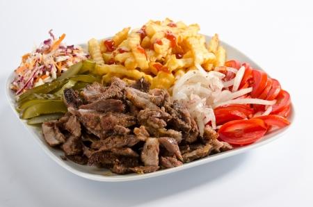 Doner kebab op een bord met frieten en salade Stockfoto