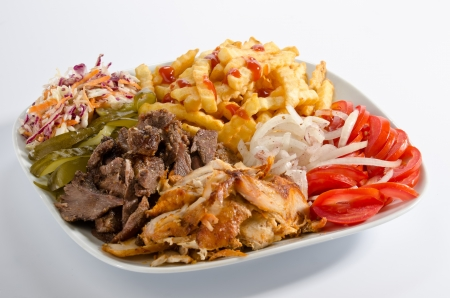 Mixed doner kebab on a plate with french fries and salad
