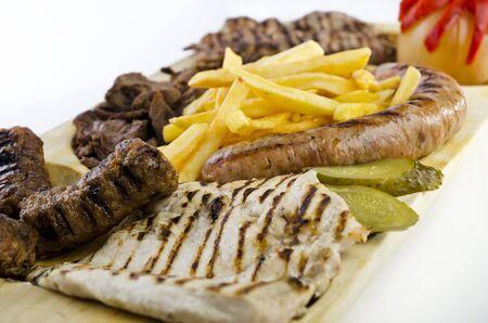 carnes y verduras: Bandeja r�stica con diversas carnes, papas fritas franc�s y verduras variadas Foto de archivo