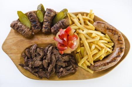 carnes y verduras: Bandeja r�stica con varias carnes, papas fritas franc�s y vegetales variados Foto de archivo