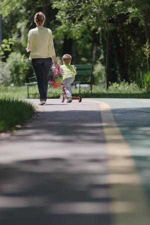 sandal tree: Kid con un scooter del empuje rodando por la l�nea junto a su madre
