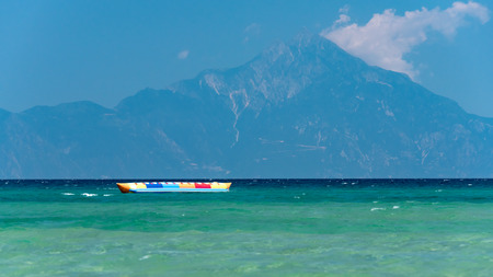 Inflatable banana shaped boat at sunset on a calm sea, Mount Athos in the background Standard-Bild