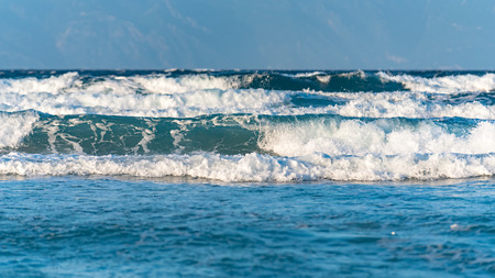 Sea waves crushing on the coast with Mount Athos in the background
