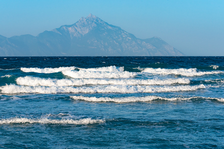 sunrise ocean: Sea waves crushing on the coast with Mount Athos in the background
