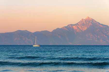 Lonely boat sailing at sunset on a calm sea, Mount Athos in the background