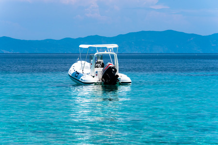 Stationary speed boats on  a calm sea, Mount Athos in the background Standard-Bild
