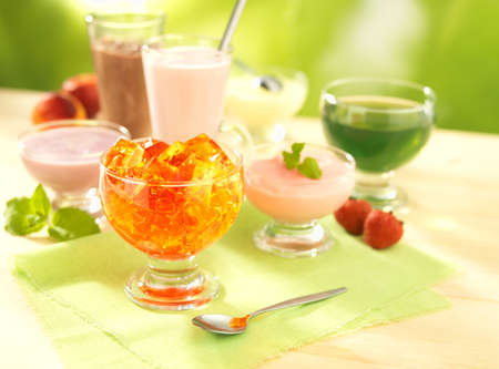 group of dairy and fruit desserts with pudding, fruit jelly, shake and joghurt on table with spoon photo