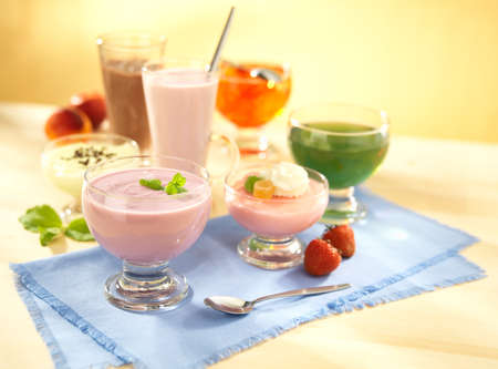 group of dairy and fruit desserts with pudding, fruit jelly, shake and joghurt on table with spoon Foto de archivo