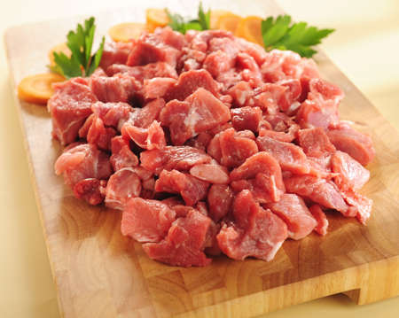 to cut: raw beef stew on a wooden cutting board.