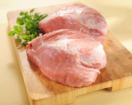 pork: raw pork shoulder on a wood cutting board.