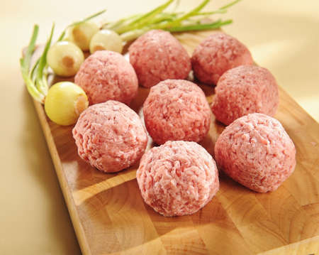 raw delicatessen minced meat on a cutting board and vegetables.