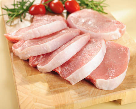 raw pork chops on a cutting board and vegetables. Stock Photo