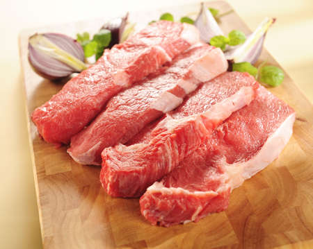 raw beef steaks. arrangement on a cutting board. Banco de Imagens