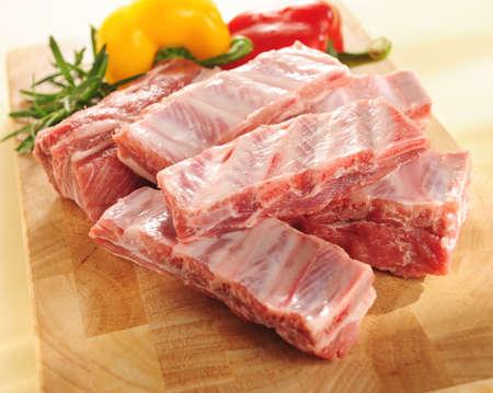charcuter�a: costillas de cerdo crudo sobre una tabla de cortar y verduras