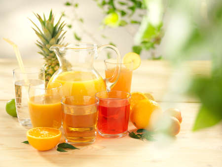 The set of different types of juices on a wooden table.
