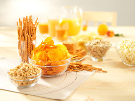 A lots of salty snacks with juice on a wooden table photo