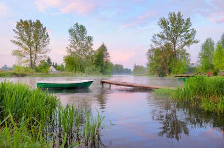 vlonder: Landelijk landschap met boot en voetgangersbrug over de Narew rivier na mist, Polen