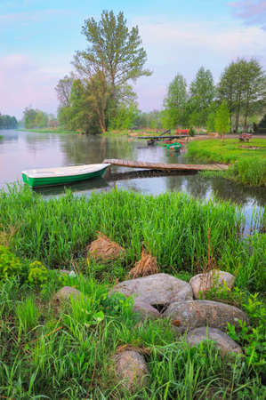 Rural landscape with boat and footbridge on the Narew river after fog, Poland  photo