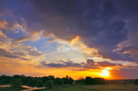 Beautiful sunrise and dramatic clouds on the sky  Flood waters of Narew river, Poland