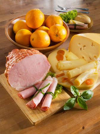charcutería: Desayuno acuerdo con jamón, queso, pan y naranjas sobre una mesa de la cocina