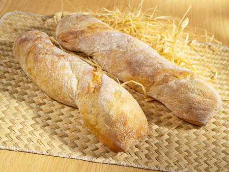 Freshly baked spicy baguette on table photo