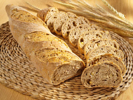 Freshly baked fitness bread and wheat on table photo