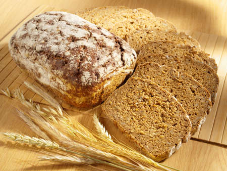 Freshly baked bread and wheat on table photo
