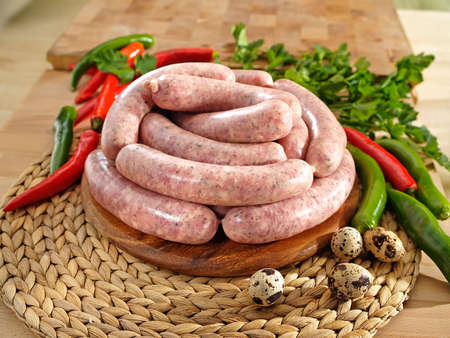 White raw sausage on a cutting board with a quail eggs Foto de archivo
