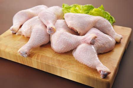 muslos: Fresh piernas de pollo crudo arreglo a bordo de la cocina de corte