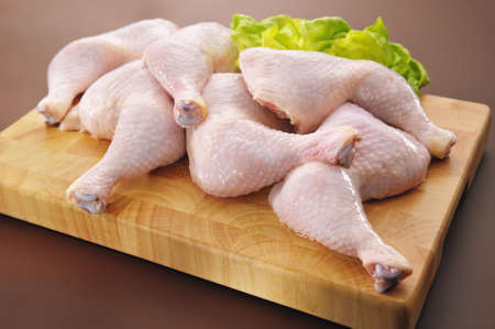 Fresh raw chicken legs arrangement on kitchen cutting board photo