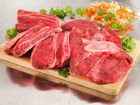 Raw beef shank steak on a cutting board and steel table