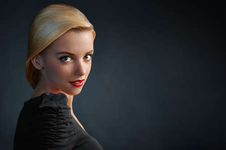 Beautiful blonde girl with red lips on dark blue background photo