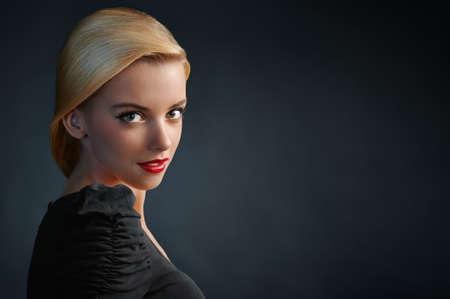 Hermosa chica rubia con labios rojos sobre fondo azul oscuro photo