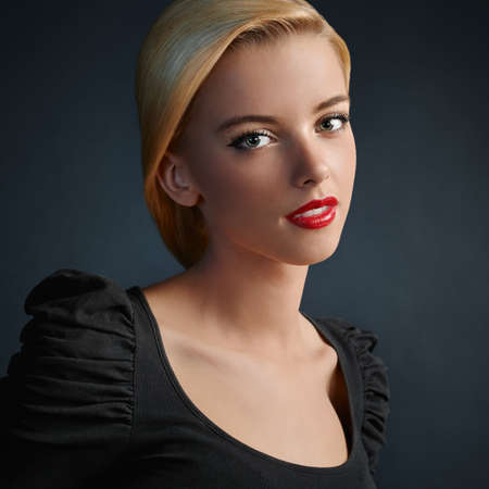 Beautiful blonde girl with red lips and modern haircut photo