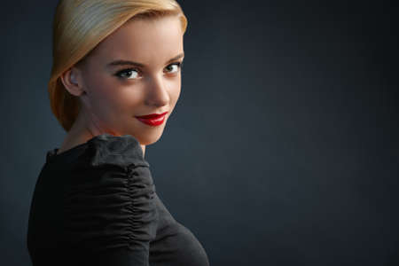 dark blond: Beautiful blonde girl with modern haircut on dark blue background with copyspace Stock Photo