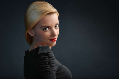 Beautiful blonde girl with modern haircut on dark blue background