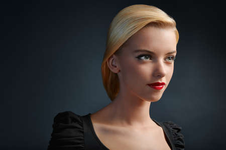 rubia ojos azules: Retrato de la hermosa chica rubia sobre fondo oscuro con copyspace
