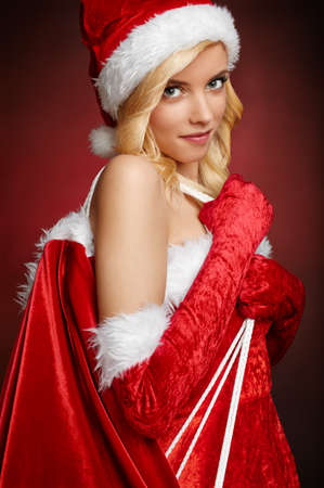 Beautiful girl with Santa Claus gift sack on red background photo
