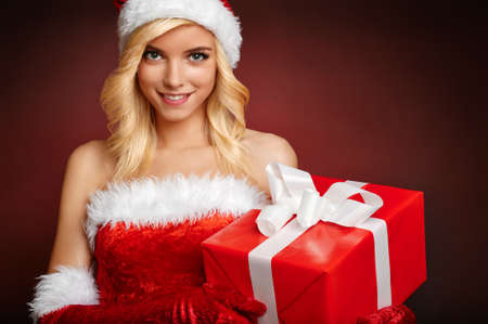 Beautiful girl with gift wearing santa claus clothes