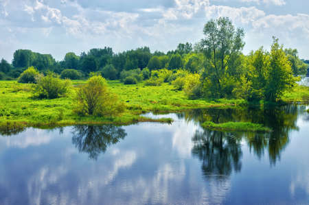 Spring landscape with river and clouds on the sky photo