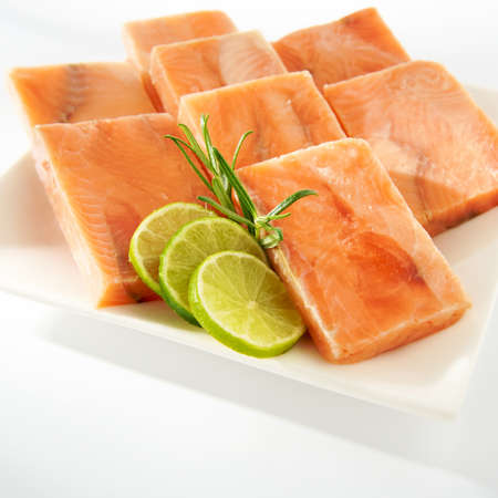 Arrangement with raw salmon cubes on plate photo