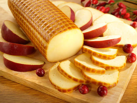 Smoked cheese on kitchen board with cranberry and apple photo