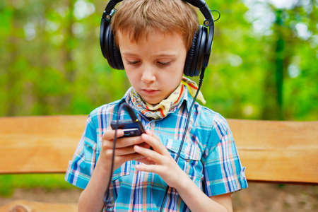 internet explorer: Young boy listening to music on stereo headphones Stock Photo