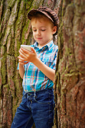 Young boy reading sms on his phone photo